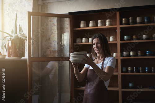 Artisan standing in her gallery with a stack of plates