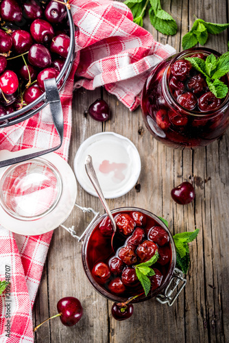 Fotobehang Kersen Homemade preserved cherry and mint jam, with fresh cherries on rustic old wooden background copy space above