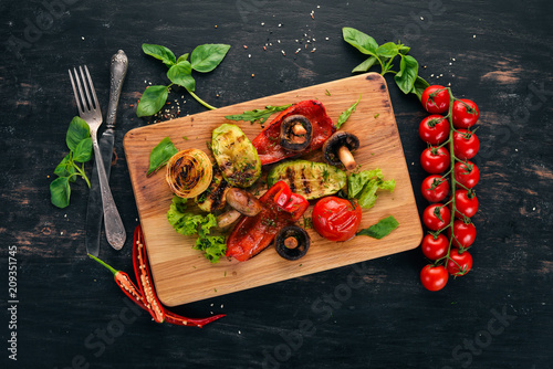 Grilled vegetables on a wooden board. On a wooden background. Top view. Copy space.