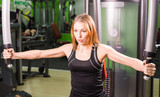 Caucasian fitness woman is working out on butterfly machine in gym