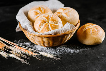 Fragrant fresh buns with wheat flakes on black wooden background