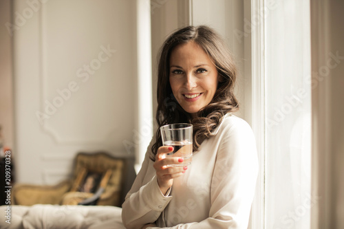 Foto Murales Smiling woman holding a glass of water