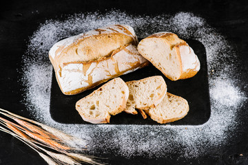 Fresh french bread on black wooden background