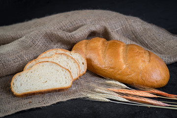 Sweet tasty bread and wheat on wooden background