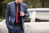 Successful businessman in a dark business suit with a red tie against the background of a car. Stylish man. Fashionable watch on hand - 209378114