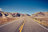 Vintage toned picture of a deserted road, travel concept, USA.