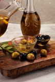 Bottle virgin olive oil and oil in a bowl with some olives - 209383912