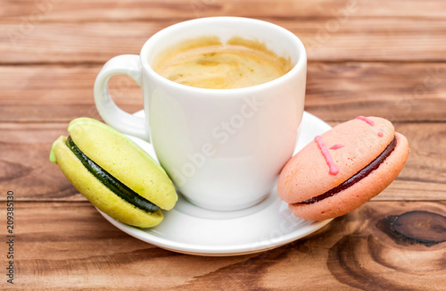Wall mural Cup of coffee with colorful macaroons on the wooden table.