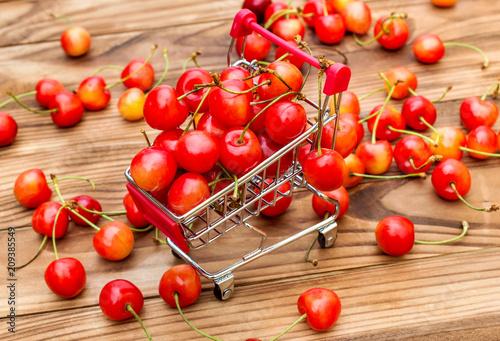 Fotobehang Kersen Shopping cart with cherries on wooden table.