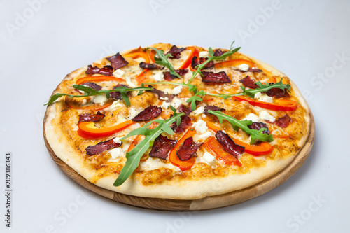 Aluminium Pizzeria appetizing pizza with bacon, cheese and pepper is decorated with arugula lays on the board