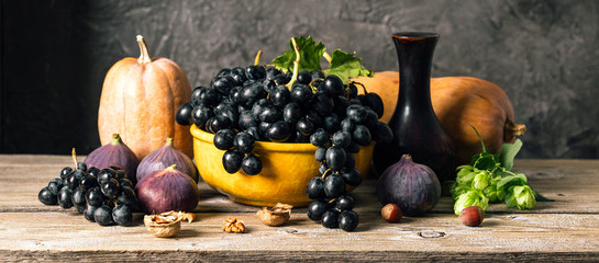 autumn still life, pumpkin, grapes, figs and nuts on a wooden table, dark background