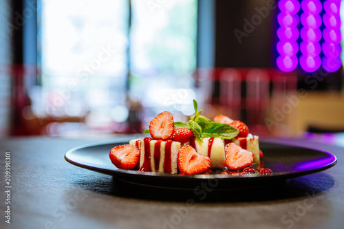 Beautiful dessert with strawberries and mint on a black plate - 209398301