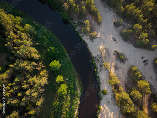 Plexiglas Zwart top view to bending river in green forest on sunse