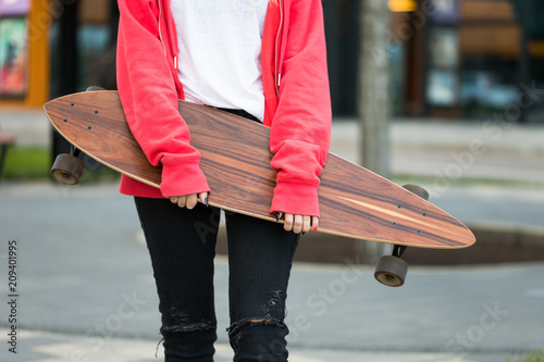 Fotobehang Skateboard Female teenager posing with skateboard or long board outdoors, cropped image, closeup.Leisure, healthy lifestyle, extreme sports concept. Stylish skateboarder with beautiful longboard in the city