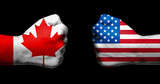 Flags of Canada and United States painted on two clenched fists facing each other on black background/Canada and USA relations concept