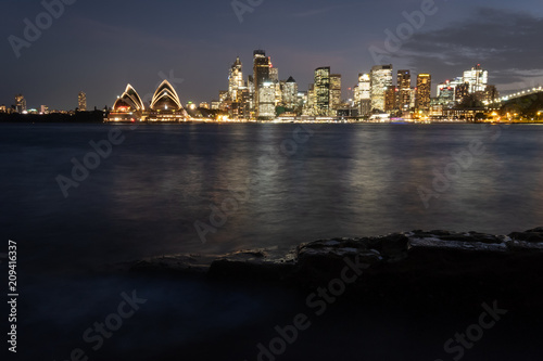 Fotobehang Sydney Sydney city lit up in the evening and spilling light over the beautiful Sydney Harbour