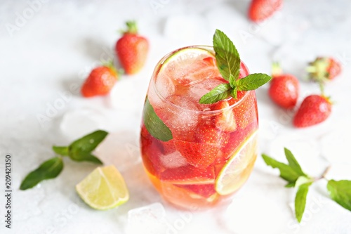 Strawberry infused water, coctail, lemonade or tea. Summer iced cold drink with strawberry, lemon and mint. Selective focus