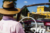 Havana, Cuba - 30 March 2018: Cuban man driving a vintage car taxi in Havana, Cuba.  Close up of a local taxi driver from the backseat.