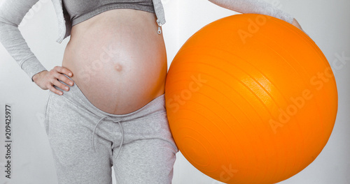 Leinwanddruck Bild Pregnant woman holding a fitness ball. Close up lady tummy