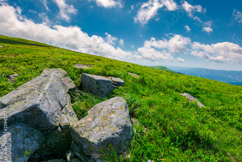 lovely summer landscape. grassy hillside with rocky formations. cloud behind the mountain peak in the distance. bright and fresh day, good mood. wonderful place for hiking and camping