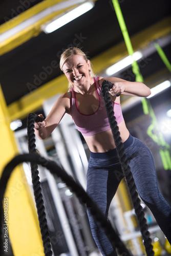 kobieta lekkoatletka robi liny bitewne krzyż ćwiczeń fitness