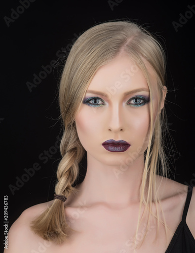 girl with blonde hair isolated on black. girl with pigtail hairdo and bright makeup