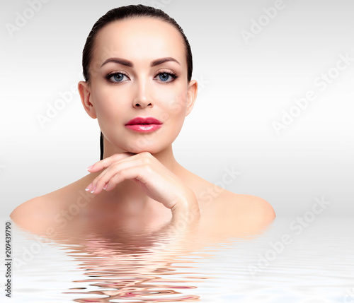 Pretty woman against a grey background with copyspace