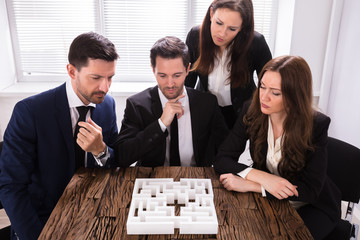 Businesspeople Trying To Solve Maze Puzzle