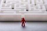 Human Figure Standing Outside Maze Entrance - 209443335