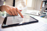 Businessperson Analyzing Invoice On Digital Tablet - 209444760