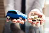 Businessperson Holding Small Blue Car And Golden Coins - 209444985