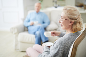 Happy senior female with cup of tea sitting in armchair and watching television with her husband on background