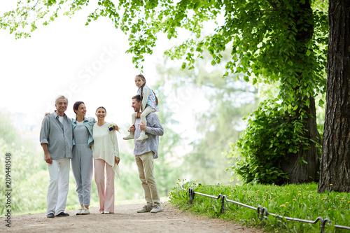 Leinwanddruck Bild Family of five spending summer day in park by walking under green foliage