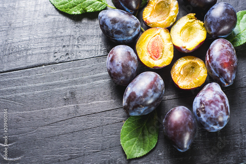Many fresh plums on black background. Copy space