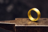 golden ring on a goldsmith anvil in the jewelry factory, close up shot with copy space in the dark background - 209451956