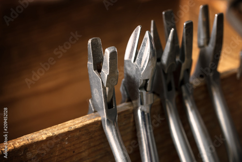 different pliers from a goldsmith on a wooden tool holder on the jewelry workplace, copy space © Maren Winter