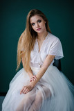Beautiful girl in a white peignoir, with long hair and amazing make up, poses in the studio loft, fine art wedding style - 209459177