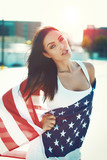 American sensual beauty covered by star spangled banner in sunset