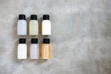 Travel-sized mini bottles cosmetic products from above on concrete table. Skincare, moisturizers, essences, body and hair treatments. Minimalism blogging concept. - 209463321