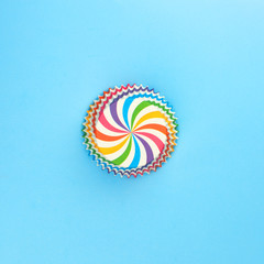 Rainbow mold for cupcake on blue background, minimal creative idea. Flat lay, top view.