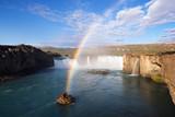 Godafoss waterfall and rainbow on a sunny morning