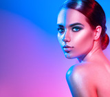 High fashion model girl in colorful bright sparkles and neon lights posing in studio. Portrait of beautiful woman, trendy glowing make-up. Art design colourful make up. Glitter vivid neon makeup - 209494937