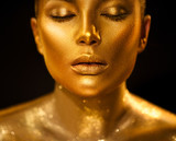 Golden skin woman face. Fashion art portrait closeup. Model girl with holiday golden glamour shiny professional makeup. Gold jewellery, jewelry, accessories. Beauty gold metallic body, lips and skin - 209494985