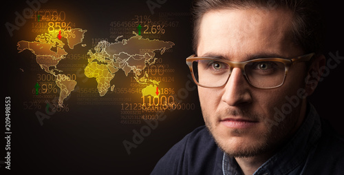 Foto Murales Portrait of a young businessman with a world map and numbers next to him on a dark background