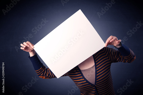 Leinwanddruck Bild Young casual woman hiding behind a blank piece of paper