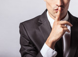 Man saying hush be quiet with finger on lips gesture isolated on gray wall background. Top secret concept. - 209503555