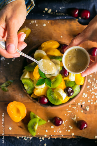 Woman hands adds sweet banana smooth cream with spoon to fruit salad in bowl on wooden board. Healthy sweet dessert for breakfast. Raw vegan vegetarian healthy food - 209514370