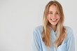 Leinwanddruck Bild - Joyful pretty young woman giggles positively at camera, dressed in casual shirt, shows beauty, poses against white background with blank copy space for your advertisement or promotional text