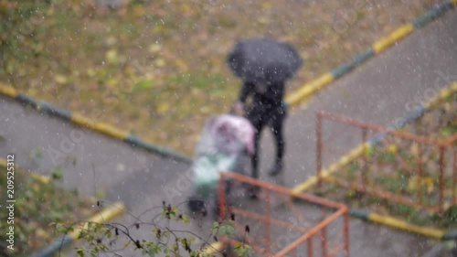 Slow motion shot of a mother with baby carriage walking outside on nasty day, snow with rain falling. Wet and chilly autumn