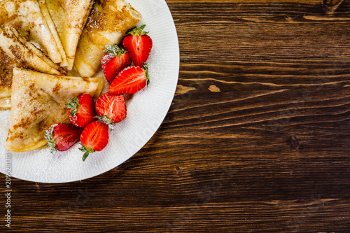 Leinwanddruck Bild Crepes with cream and strawberries